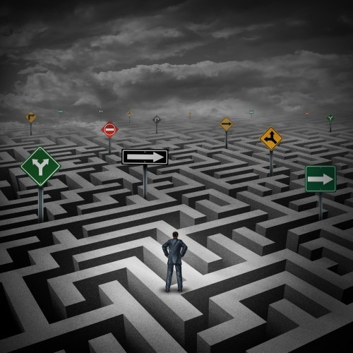 Strategy Crisis Concept As A Businessman Standing On A Three Dimensional Maze Or Labyrinth With Confusing Direction Road Signs As A Metaphor For Facing Difficulties In Business And The Stress Of Daily Life.